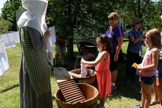 Young fans of Laura Ingalls Wilder experiment with wooden washboards at Genesee Country Village & Museum's Laura Ingalls Wilder Days. Photo by Ruby Foote.