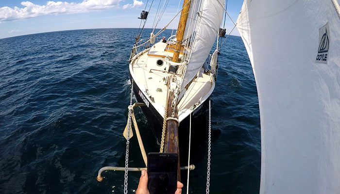 This photo shows a smart phone in the foreground as I use the Go Pro app to frame the video of the boat under sail.