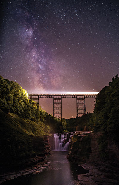"Grand Prize ""Lighting the Way"" ""I was at Letchworth State Park to photograph the Milky Way and was surprised and delighted when a cargo train crossed the Portageville Bridge. This is the shot of a lifetime for me."" Mandy Applin • Pittsford"