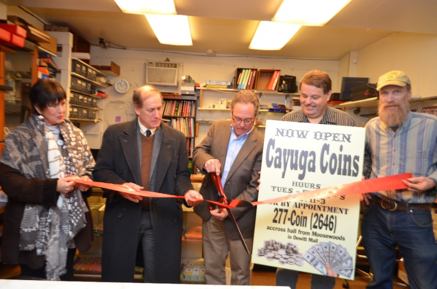 City of Ithaca Economic Development Deputy Director Phyllisa DeSarno (left), Downtown Ithaca Alliance Executive Gary Ferguson, Cayuga Coins owner Bob Lisk and his business partner Frank Anderson watch as City of Ithaca Common Council 3rd Ward Alderman Rob Gearhart prepares to cut a ribbon during a ceremony held at Cayuga Coins on Wednesday. The ceremony marks the grand opening of Cayuga Coins. The coin and stamp shop opened in the Fall and is located in Dewitt Mall.